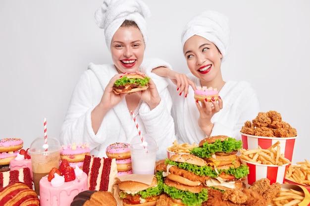 Glückliche frauen genießen cheat-mahlzeit, essen leckere burger-kuchen und donuts, die süchtig nach fast food sind