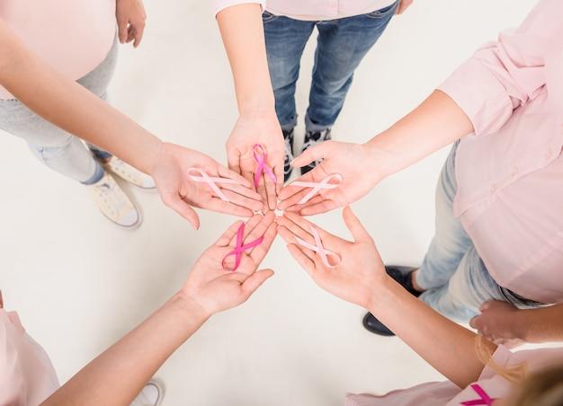 Glückliche frauen im kreis mit rosa bändern für brustkrebs.