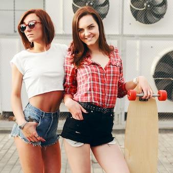 Glückliche frauen in kurzen hosen mit einem skateboard im freien