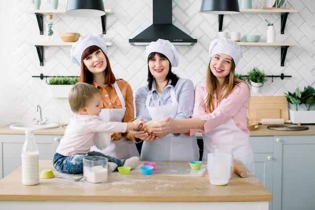 Glückliche frauen in weißen schürzen backen zusammen und halten den teig in den händen in der hellen küche. kleines mädchen hilft, zusammen mit mutter, tante und großmutter cupcakes zu machen