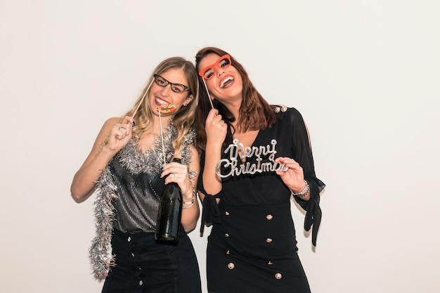 Glückliche frauen mit aufschrift der frohen weihnachten auf party