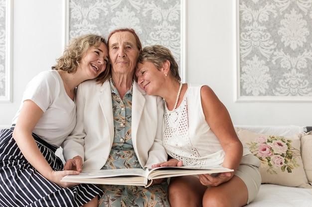 Glückliche frauen mit drei generationen, die auf sofa mit dem halten des fotoalbums sitzen