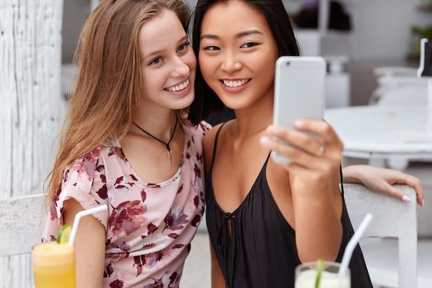 Glückliche frauen mit einem angenehmen lächeln machen ein foto auf dem handy, verbringen ihre freizeit zusammen in der cafeteria und trinken frische cocktails. genießen sie den urlaub im resort.