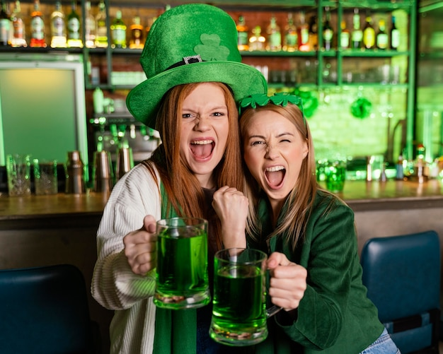 Glückliche frauen mit hut feiern st. patricks tag an der bar mit getränken