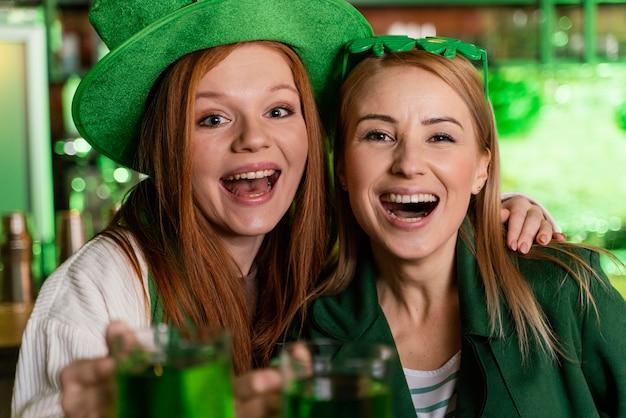 Glückliche frauen mit hut feiern st. patricks tag an der bar