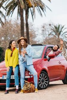 Glückliche frauen mit smartphone nahe dem mann, der sich heraus vom auto lehnt