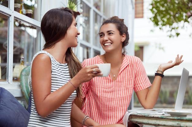 Glückliche frauen ruhen sich während der kaffeepause aus, besprechen ihr zukünftiges projekt und benutzen einen modernen laptop. beste freunde treffen sich im café, schauen sich freudig an, unterhalten sich angenehm
