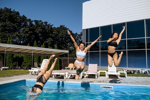 Glückliche frauen springen im freien in den pool, blick in bewegung