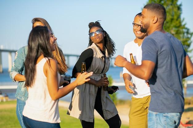Glückliche frauen und männer, die in park am abend tanzen. freundliche freunde, die mit bier während des sonnenuntergangs sich entspannen. freizeit-konzept