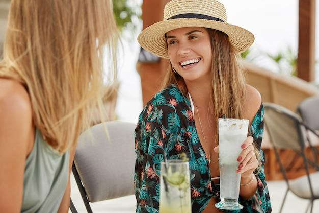 Glückliche frauen unterhalten sich angenehm, während sie sich auf einer sommerparty treffen, alkoholische cocktails trinken, sich über urlaub oder freien tag freuen und sich mit fröhlichem ausdruck ansehen. menschen- und freizeitkonzept