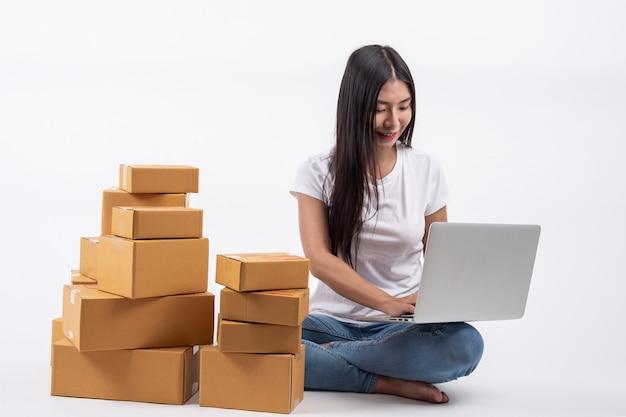 Glückliche frauen von der bestellung von produkten von kunden, unternehmer, die zu hause an einem weißen backg arbeiten