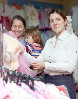 Glückliche frauen wählt abnutzung am kleidergeschäft. fokus auf frau