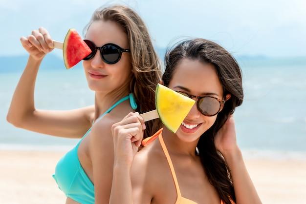 Glückliche frauenfreunde mit wassermelonenfrucht am strand im sommer
