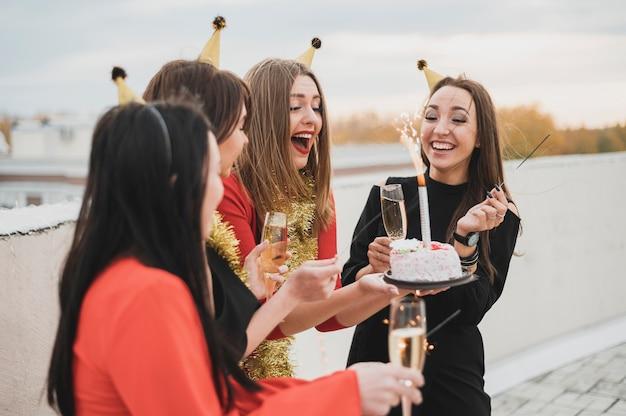 Glückliche frauengruppe, die den geburtstag auf der dachspitze feiert