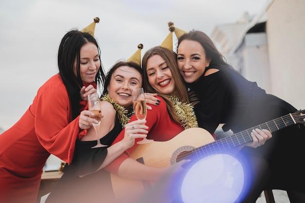Glückliche frauengruppe, welche die gitarre auf der dachspitzenparty spielt