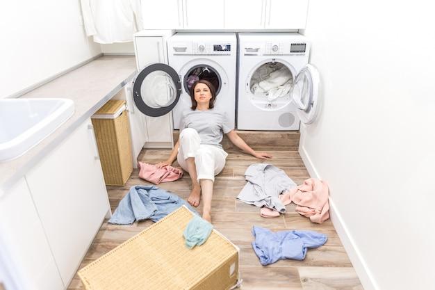 Glückliche frauenhausfrau in der waschküche nahe der waschmaschine mit schmutziger kleidung