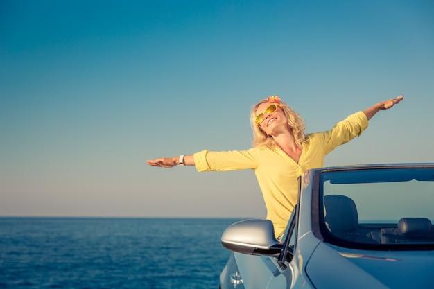 Glückliche frauenreise mit dem auto person, die spaß im blauen cabriolet-sommerferienkonzept hat
