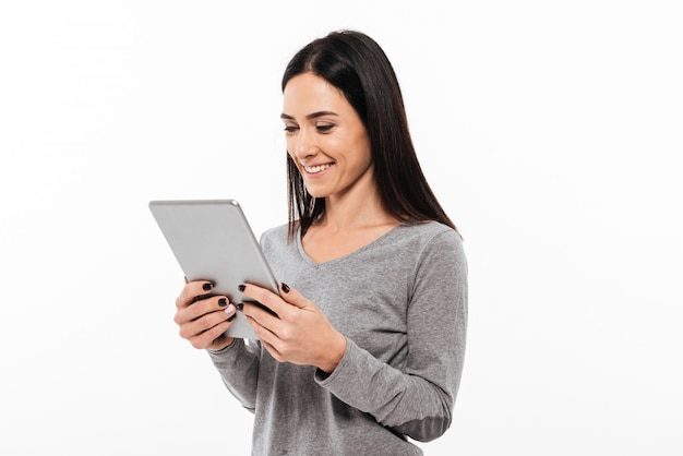 Glückliche frauenstellung lokalisiert unter verwendung des tablet-computers.