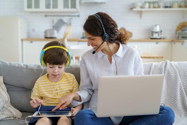 Glückliche freiberufliche mutter mit kind, das auf couch zu hause büroarbeit auf laptop sitzt.
