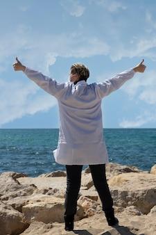 Glückliche freiheit blonde doktorfrau mit offenen armen, die draußen mit hoffnung auf blauen meereshorizont schaut. unbeschwerter russisch-kaukasischer amerikanischer arzt in medizinischer maske und weißem kittel mit dem rücken zur kamera
