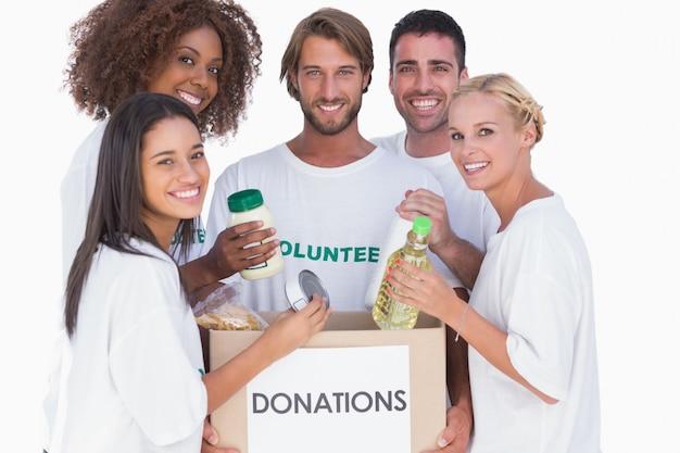 Glückliche freiwillige, die lebensmittel in spendenkasten einsetzen
