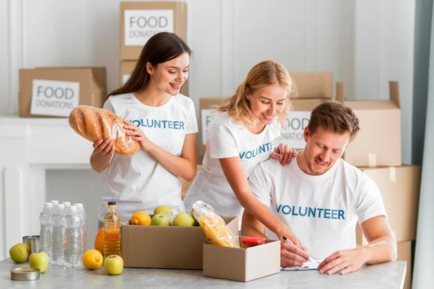 Glückliche freiwillige, die mit lebensmittelspenden helfen