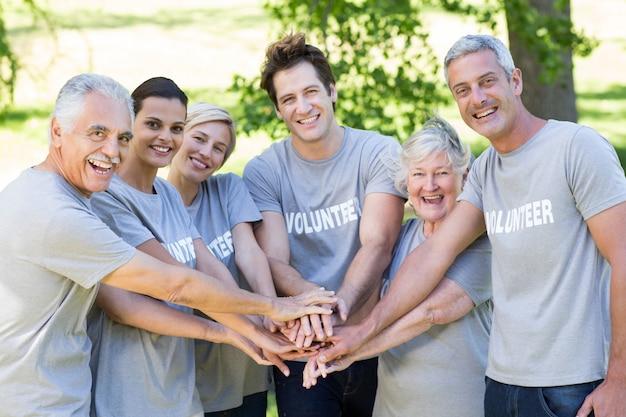 Glückliche freiwillige familie, die ihre hände zusammenfügt