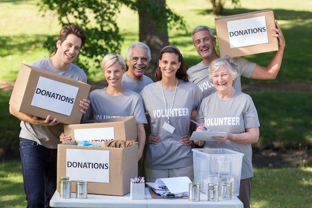 Glückliche freiwillige familie, die spendenkästen hält