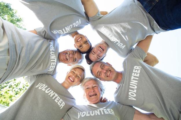 Glückliche freiwillige familie, die unten der kamera betrachtet