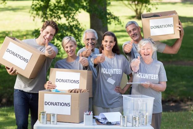 Glückliche freiwillige familie mit daumen hoch