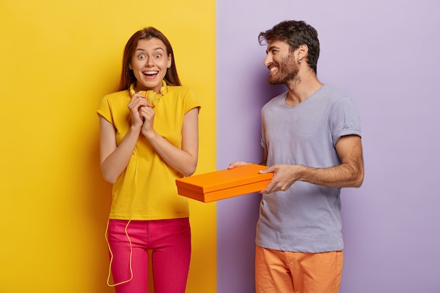 Glückliche freudige brünette junge frau hält hände zusammen, trägt gelbes freizeithemd und rosa hose, erhält pappkarton vom freund