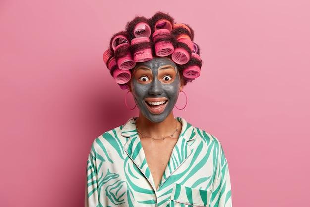 Glückliche freudige frau besucht friseur- und spa-salon, macht perfekte frisur und trägt tongesichtsmaske auf, trägt pyjama, hat ausdruck überrascht, isoliert auf rosa. frau geht auf date