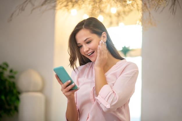 Glückliche freudige frau, die ihre wange berührt, während sie mit einem smartphone in ihren händen steht