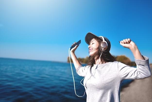 Glückliche freudige frau, die musik hört, während sie im freien nahe dem meer ist