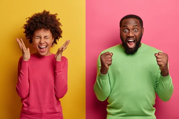 Glückliche freudige frau hebt handflächen nahe gesicht, emotional aufgeregter bärtiger afroamerikanischer mann ballt fäuste und ruft hurra aus, unterstützt lieblingsfußballmannschaft. menschen, emotionen, reaktionskonzept