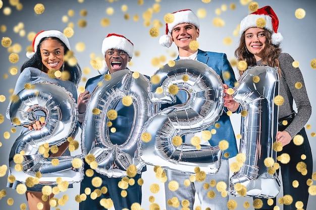 Glückliche freudige freunde mit silbernen luftballons und konfetti, die partei über grauem hintergrund haben. neujahrskonzept