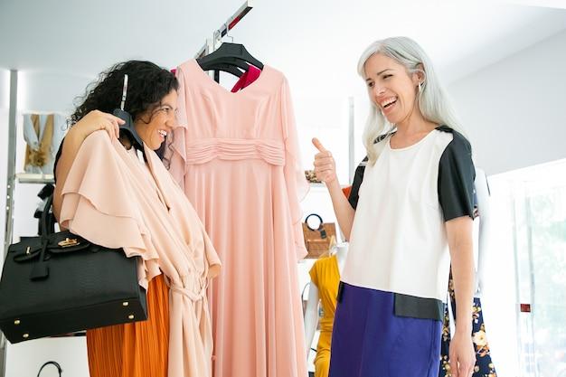 Glückliche freudige freundinnen, die zusammen einkaufen und ausgewähltes kleid im modegeschäft besprechen. verkäufer genehmigt kundenauswahl und zeigt daumen nach oben. konsum- oder einkaufskonzept