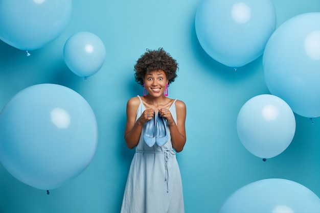 Glückliche freudige junge frau trägt blaues kleid, modische schuhe, wählt outfit und schuhe in einer farbe, wird geburtstag feiern, posiert