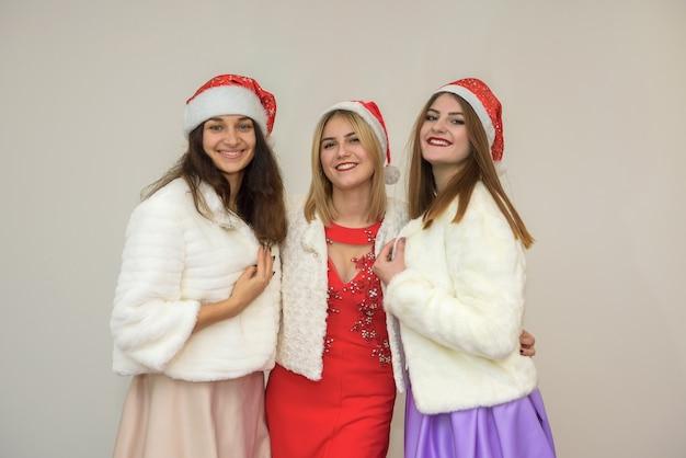 Glückliche freunde bei der neujahrsparty feiern. drei frauen in eleganten abendkleidern und pelzjacken