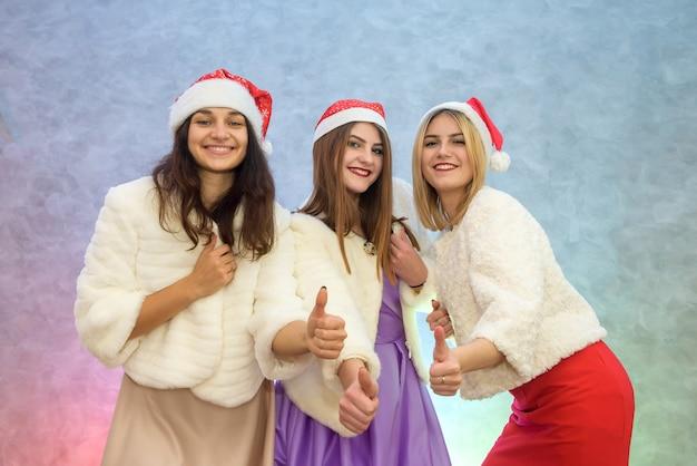 Glückliche freunde beim feiern des neuen jahres. drei frauen in eleganten abendkleidern und pelzjacken