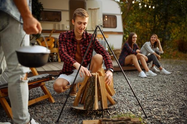 Glückliche freunde bereiten sich auf das kochen am lagerfeuer und das picknick auf dem campingplatz im wald vor. jugend mit sommerabenteuer auf wohnmobil, campingauto zwei paare freizeit, reisen mit anhänger