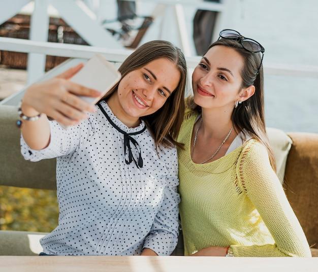 Glückliche freunde des mittleren schusses, die ein selfie nehmen