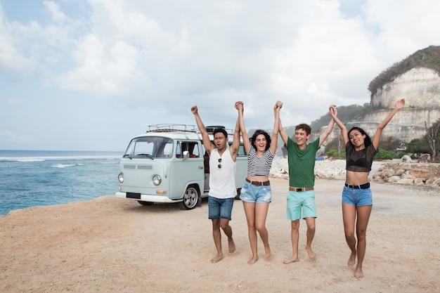 Glückliche freunde, die am strand gehen und hände erheben