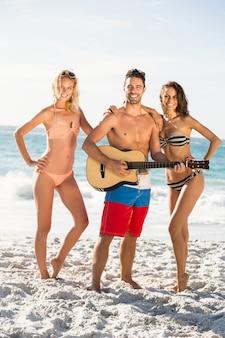 Glückliche freunde, die am strand posieren und gitarre spielen