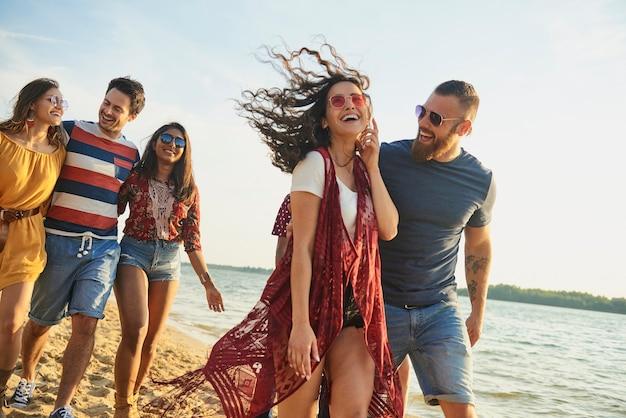 Glückliche freunde, die am strand spazieren gehen.