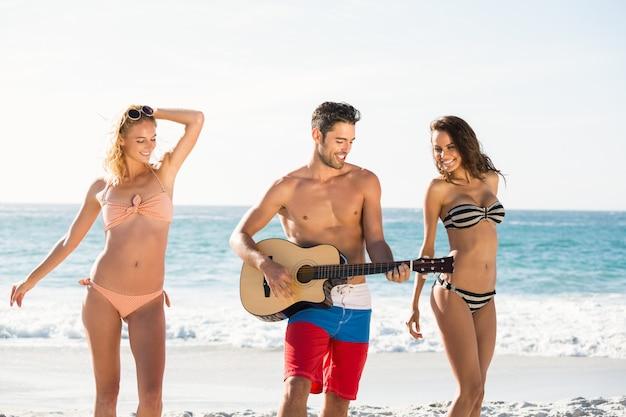 Glückliche freunde, die am strand tanzen und gitarre spielen