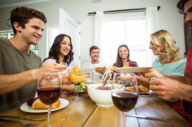 Glückliche freunde, die am tisch zu mittag essen