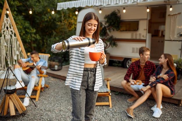 Glückliche freunde, die auf picknick, wochenende auf dem campingplatz im wald ruhen. jugend mit sommerabenteuer auf wohnmobil, campingauto zwei paare freizeit, reisen mit anhänger