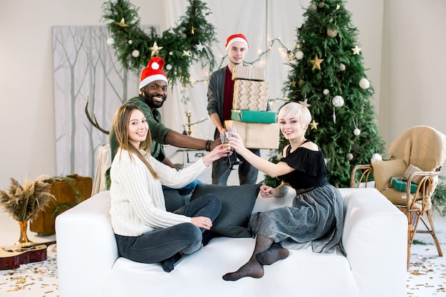 Glückliche freunde, die auf sofa zu hause sitzen, champagner trinken und weihnachtsferien genießen