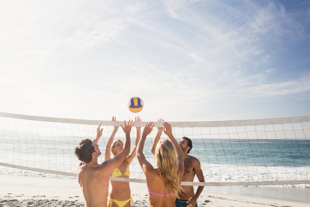 Glückliche freunde, die beachvolleyball spielen